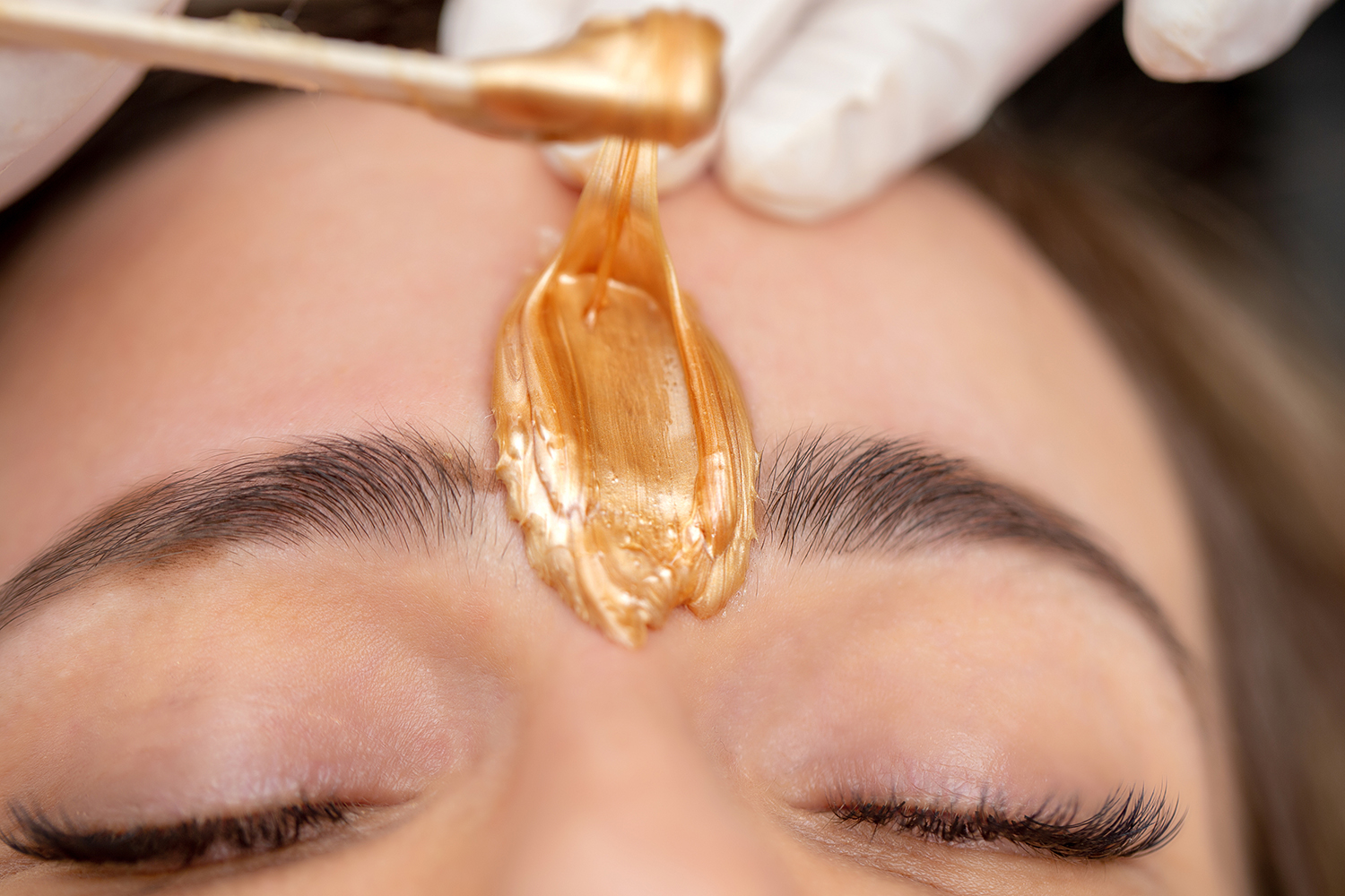 Applying Facial Wax Between Eyebrows - stock photo